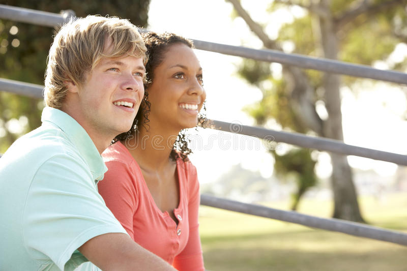Teenage Couple Sitting In Playground Stock Images