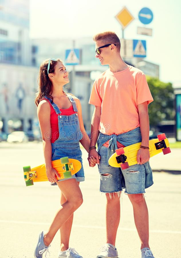 Teenage couple with skateboards on city street. Summer holidays, extreme sport and people concept - happy teenage couple with short modern cruiser skateboards on stock image