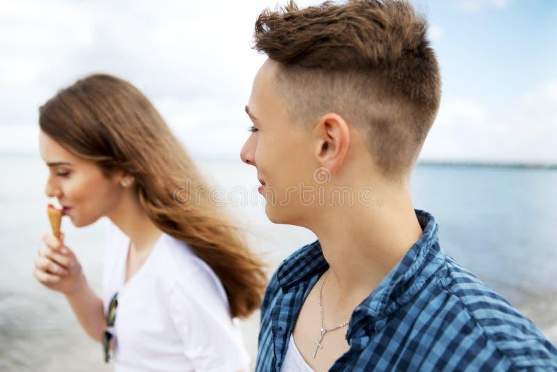 Teenage couple at seaside. Teenage couple walking on coast, sea siade royalty free stock photo