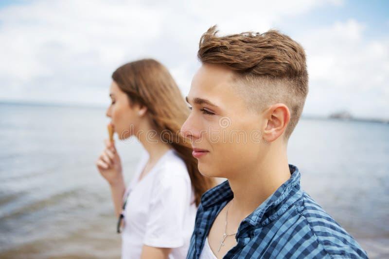Teenage couple at seaside. Teenage couple walking on coast, sea siade stock image