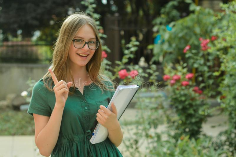 Teenage, cute young girl student in black eyeglasses, holding books. Summer holidays, education, concept - smiling female student royalty free stock photos