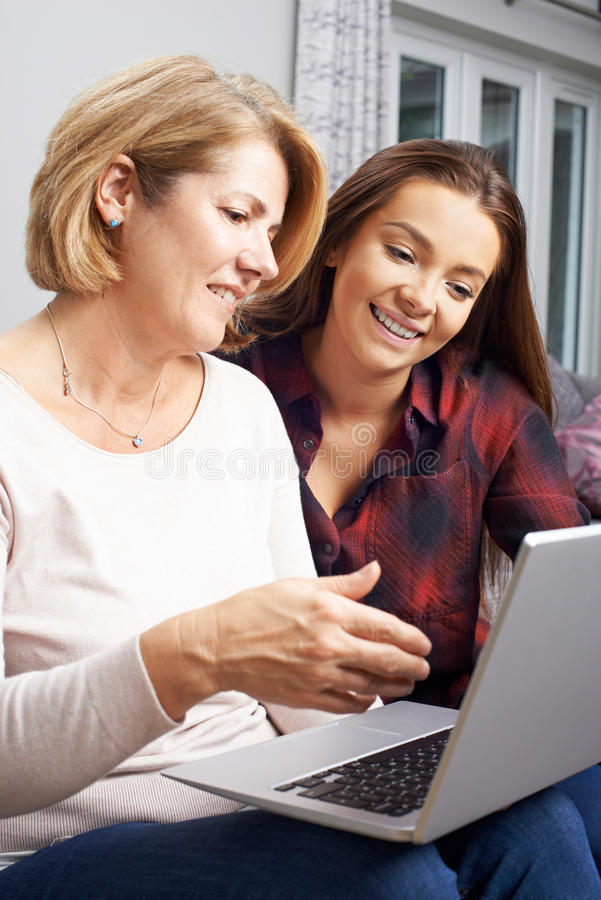 Teenage Daughter Showing Mother How To Use Laptop Computer. Teenage Daughter Shows Mother How To Use Laptop Computer stock photo