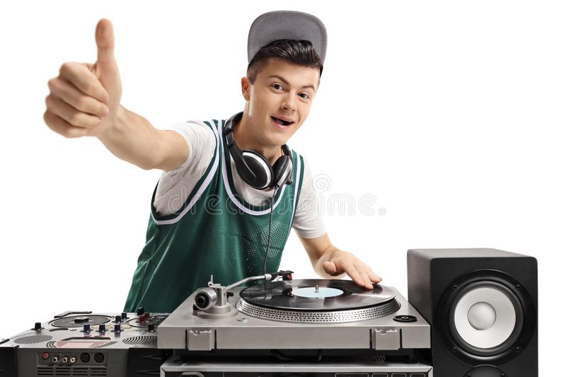 Teenage DJ playing music on a turntable. And making a thumb up sign isolated on white background royalty free stock photos