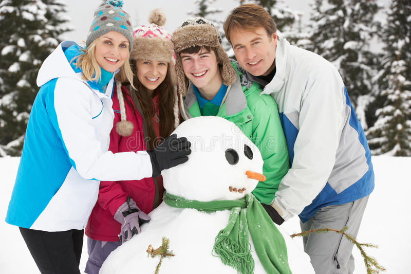 Teenage Family Building Snowman On Ski Holiday royalty free stock photo