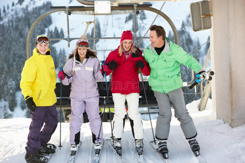 Teenage Family Getting Off Chair Lift On Holiday. Teenage Family Getting Off Chair Lift On Ski Holiday In Mountains royalty free stock photography