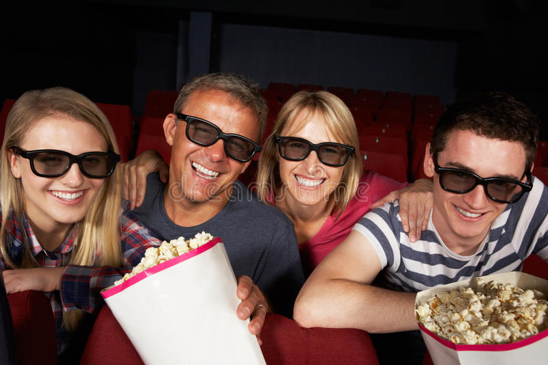 Teenage Family Watching Film In Cinema stock photography