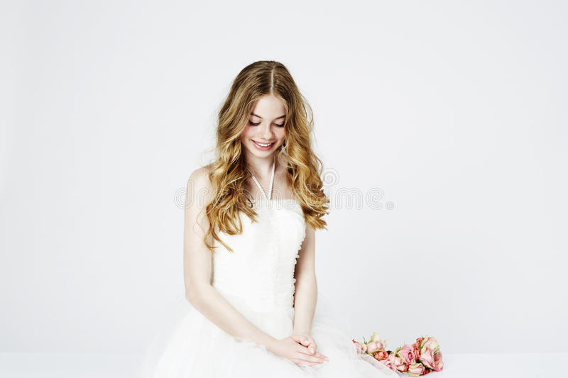 Teenage flower girl in white. Dress, looking down stock photography