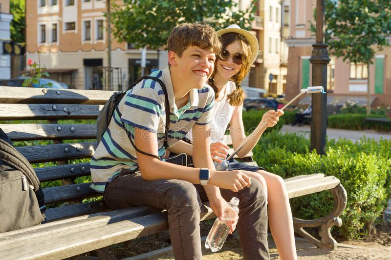 Teenage friends girl and boy sitting on bench in city, smiling, talking, looking in phone. Friendship and people concept stock image