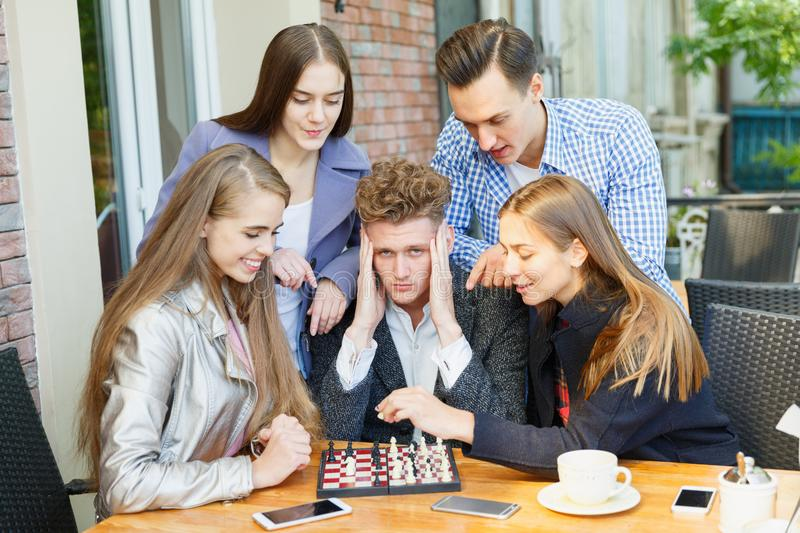 Teenage friends playing a chess game and thinking on a cafe background. Chess play concept. Five smart, gorgeous young friends playing chess on a blurred cafe stock image