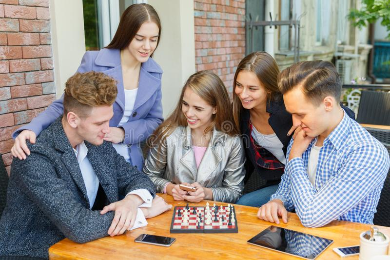 Teenage friends playing a chess game and thinking on a cafe background. Chess play concept. Five smart, gorgeous young friends playing chess on a blurred cafe stock photo
