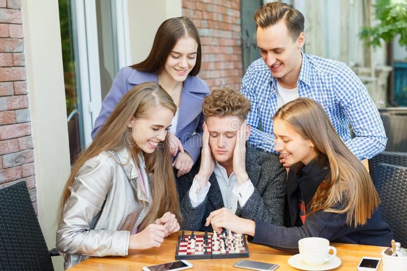 Teenage friends playing a chess game and thinking on a cafe background. Chess play concept. Five smart, gorgeous young friends playing chess on a blurred cafe royalty free stock images