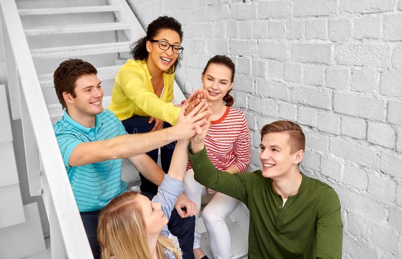 Teenage friends or students making high five stock photo