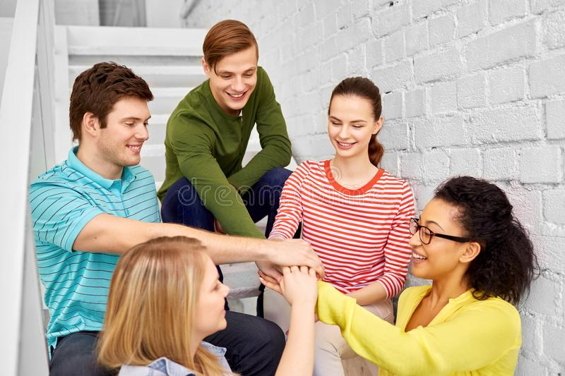 Teenage friends or students stacking hands stock image