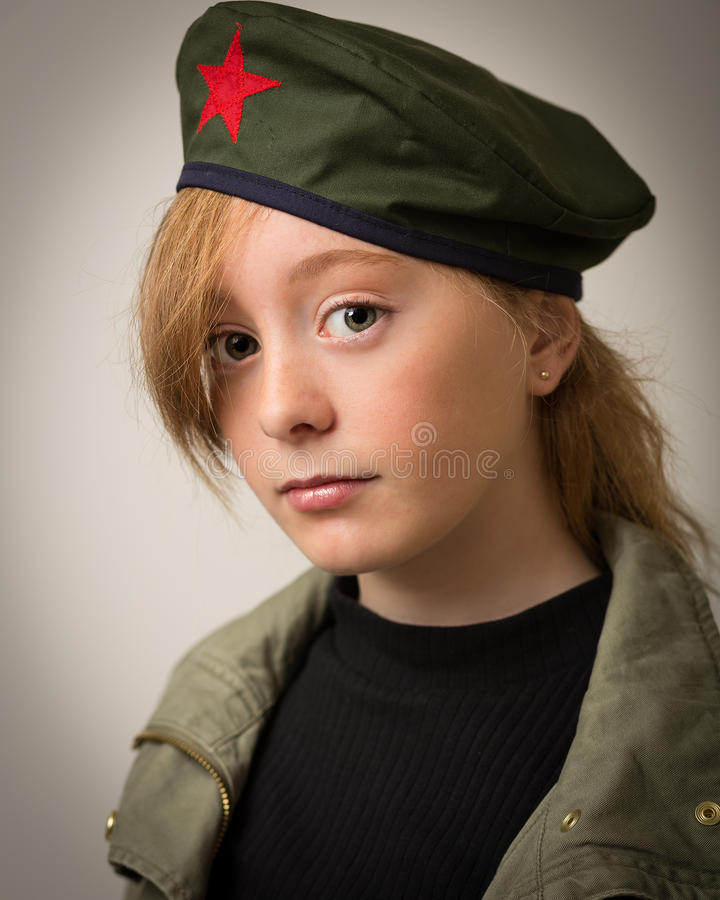 Teenage Ginger Girl In Revolution Barret Hat. Studio portrait of a teenage ginger girl with long hair wearing a Che revolution barret hat and a green army jacket stock photography