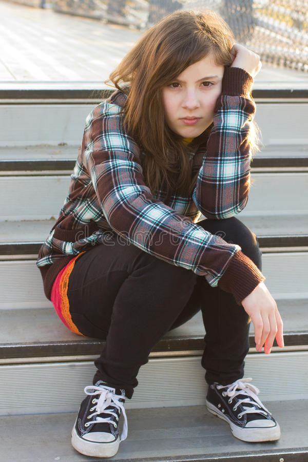 Teenage Girl. A cute teenage girl sitting on the bleachers with a serious expression stock image