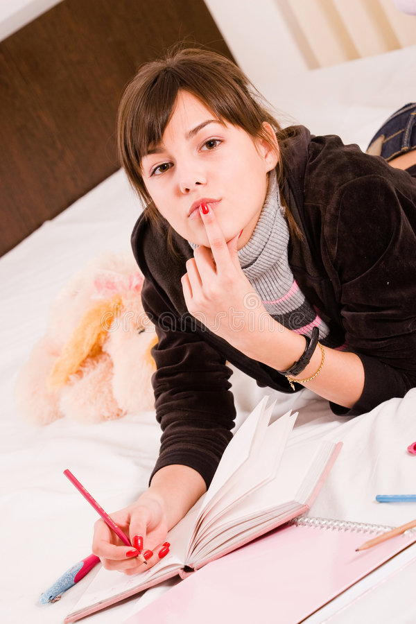 Teenage girl. Standing in her bed with her diary, holding her finger at mouth stock photos