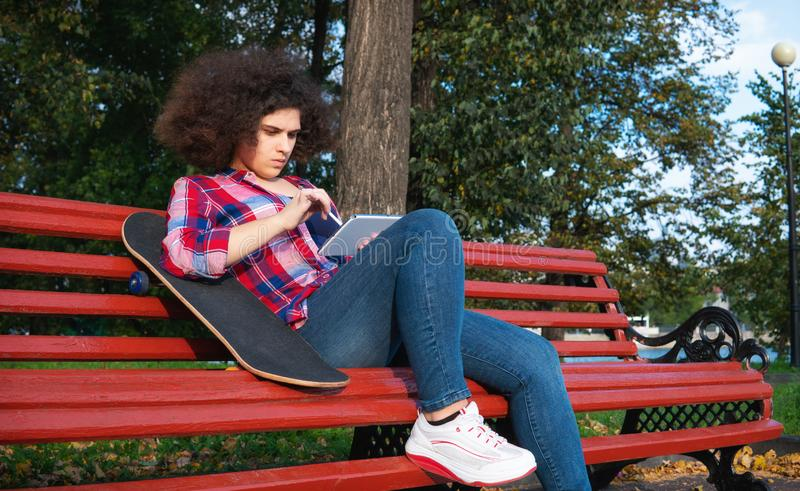 A teenage girl sits on a park bench with a skateboard and uses a tablet. royalty free stock image