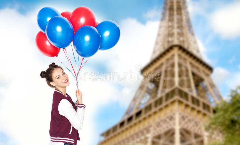 Teenage girl with balloons over eiffel tower. People, travel, tourism and holidays concept - happy smiling pretty teenage girl with helium balloons over eiffel stock images
