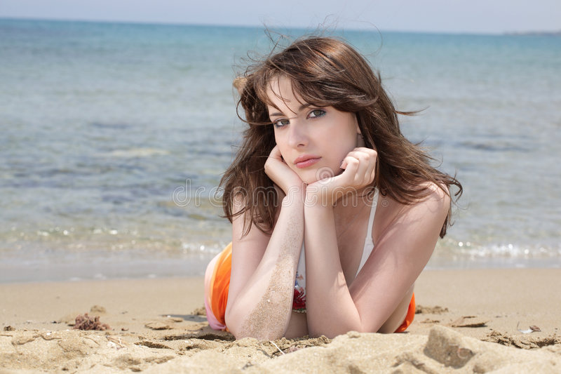 Teenage Girl on the Beach. A teenage girl laying on the beach stock images