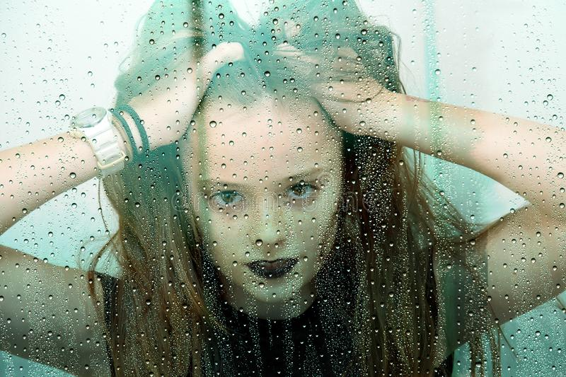 Teenage girl behind window with raindrops tousles her hair royalty free stock photo