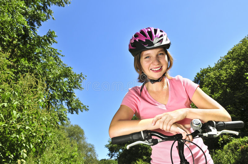 Teenage girl on a bicycle. Portrait of a teenage girl on a bicycle in summer park outdoors royalty free stock photos