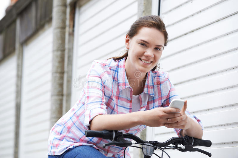 Teenage Girl On Bike Texting On Mobile Phone stock photography