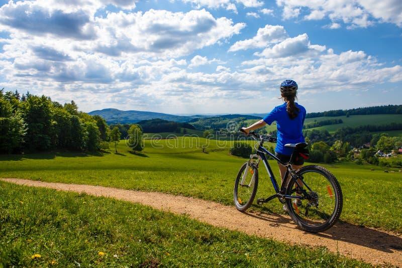 Teenage girl biking on forest trails stock photos