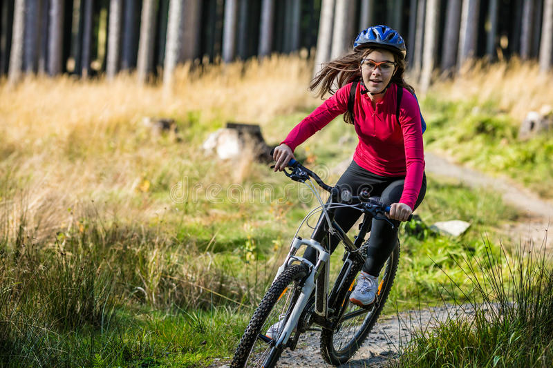 Teenage girl biking on forest trails royalty free stock photos