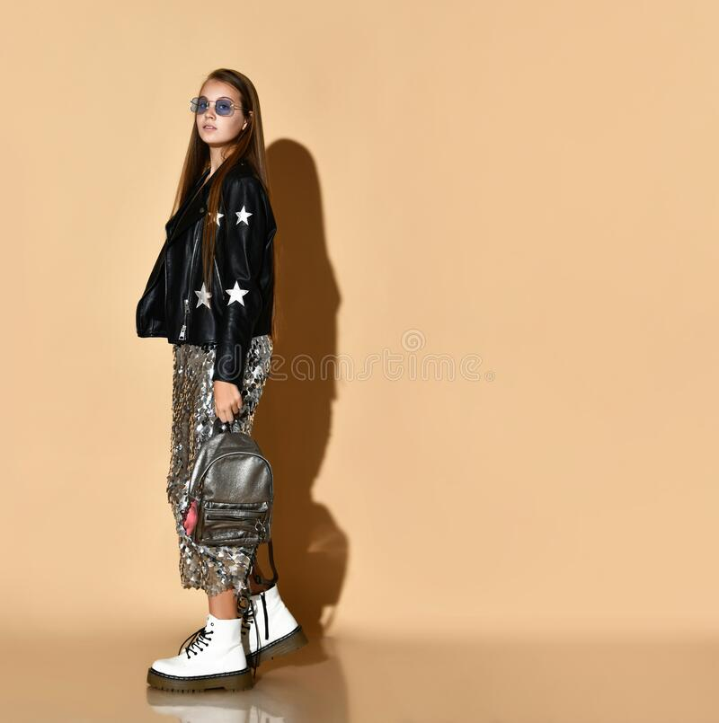 Teenage girl in black leather jacket, shiny skirt, sunglasses, white boots. Posing with silver backpack on beige background. stock photos