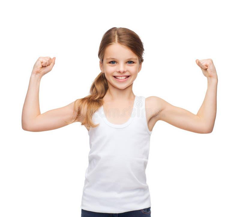 Teenage girl in blank white shirt showing muscles. Shirt design, stamina, strength, health, sport, fitness concept - smiling teenage girl in blank white shirt stock photo