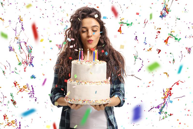 Teenage girl blowing candles on a birthday cake with confetti st royalty free stock photo