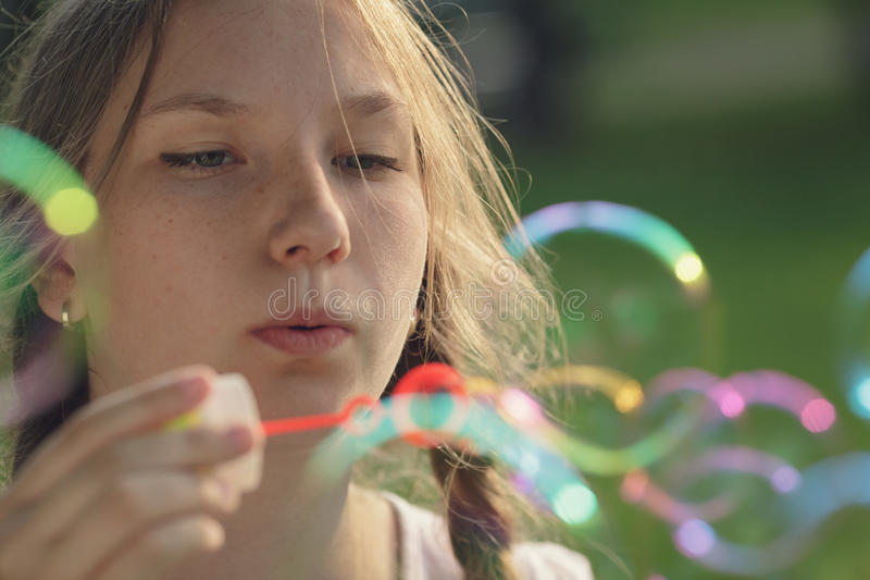 Teenage girl blows soap babbles in te park. Summertime stock photos