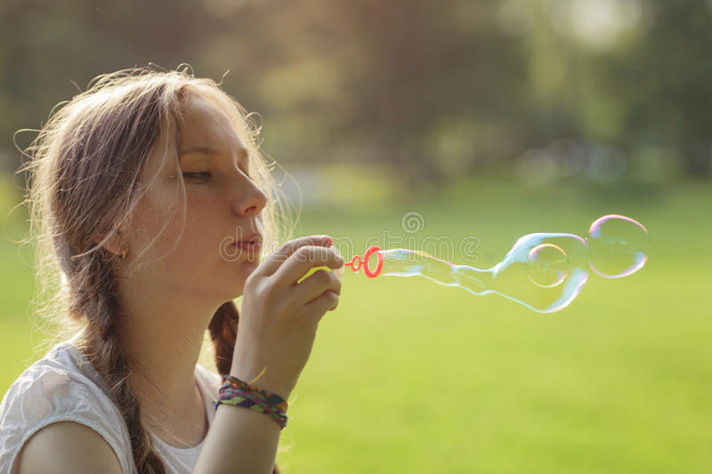 Teenage girl blows soap babbles in te park. Summertime royalty free stock photos