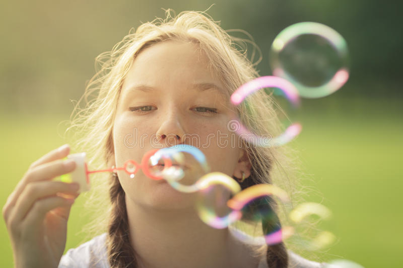 Teenage girl blows soap babbles in te park. Summertime stock photo
