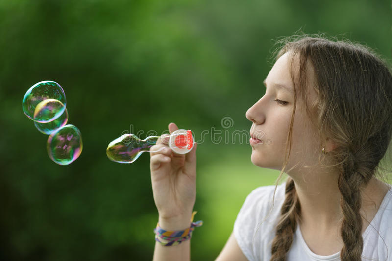 Teenage girl blows soap babbles in te park. Summertime stock images
