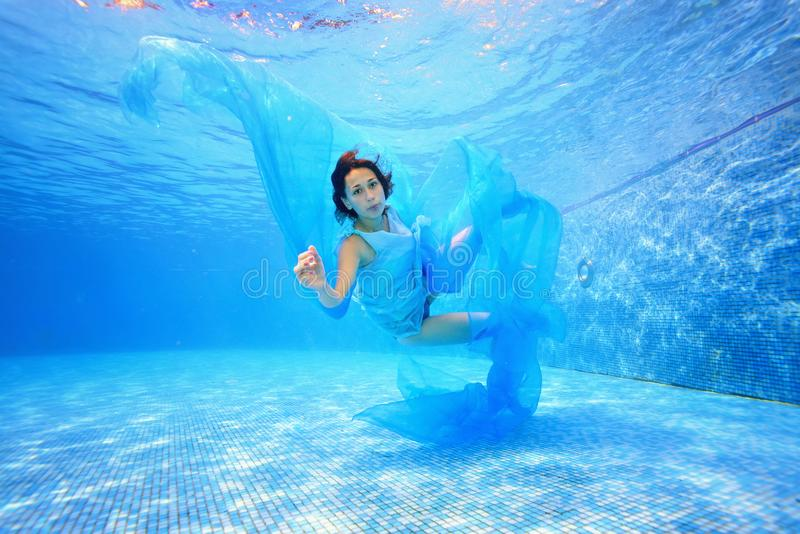 A teenage girl in a blue dress and with a blue cloth in her hand swims underwater in the pool against a blue background stock photography