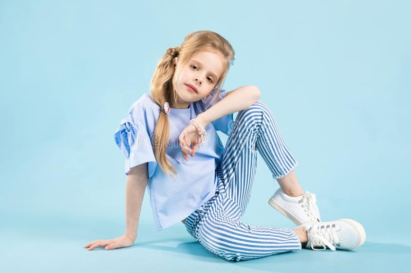 A girl in blue clothes is sitting on a blue background. stock photos