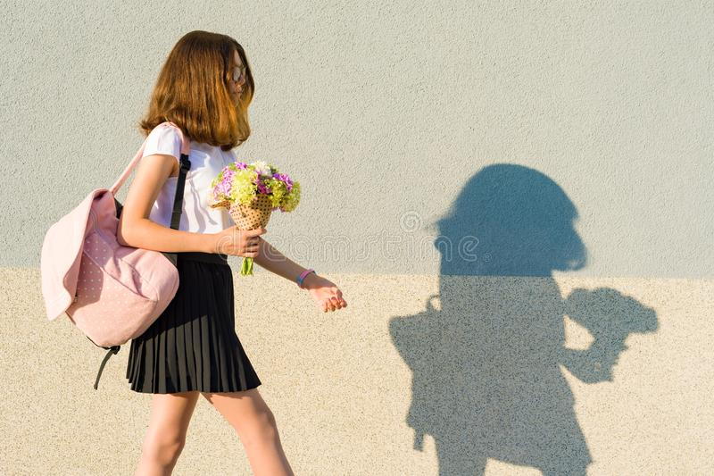 Teenage girl with bouquet, backpack. Goes against the gray wall, copy space. royalty free stock photo