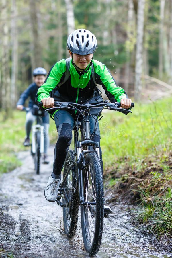 Teenage girl and boy biking on forest trails stock photography