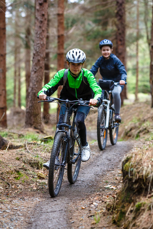 Teenage girl and boy biking on forest trails royalty free stock photos
