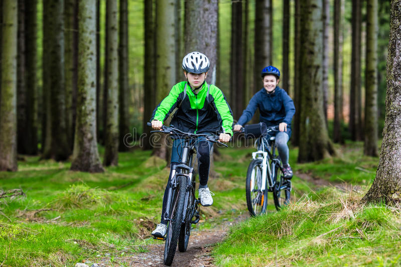 Teenage girl and boy biking on forest trails stock images