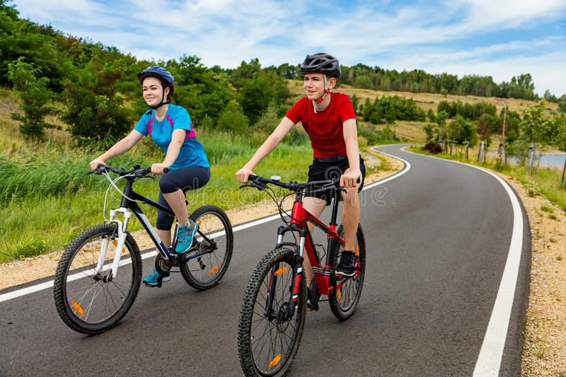 Teenage girl and boy cycling. Teenage girl and boy riding bikes royalty free stock image