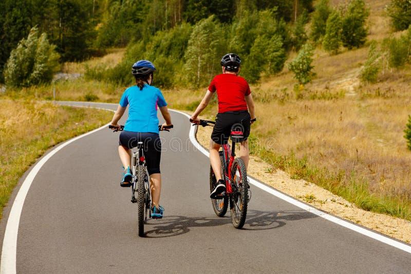 Teenage girl and boy cycling stock image