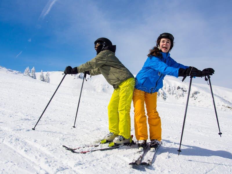 Teenage girl and boy skiing royalty free stock photo