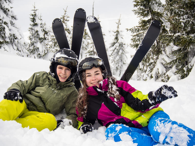 Teenage girl and boy skiing stock image