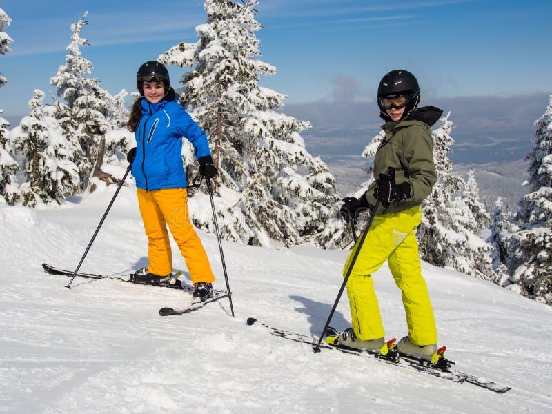 Teenage girl and boy skiing royalty free stock photos