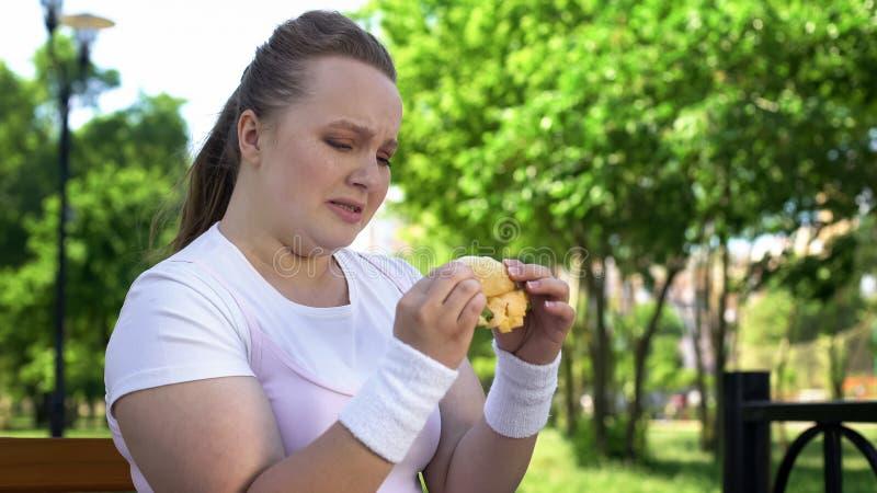 Teenage girl cannot resist temptation to eat hamburger, addiction to junk food. Stock photo royalty free stock photography