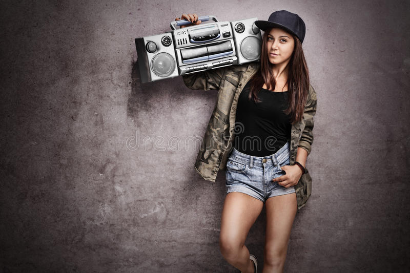 Teenage girl carrying a ghetto blaster. Over her shoulder and leaning against a rusty gray wall royalty free stock image