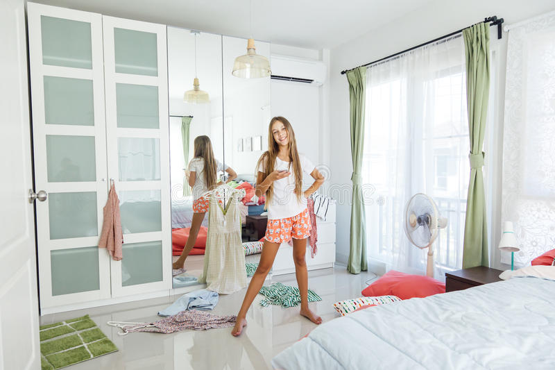 10 Years Old Pre Teen Girl Choosing Outfit In Her Closet. Messy In The  Bedroom, Clothing On The Floor. Teenager Is Dressing Up And Singing In The  Morning.