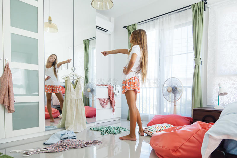 Teenage Girl Choosing Clothing In Closet Stock Image